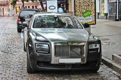 5-ое августа 2012, Киев, автомобиль призрака Rolls Royce английский на предпосылке великобританского автобуса Автомобиль в дожде стоковое фото