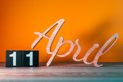 11-ое апреля День 11 месяца, ежедневного деревянного календаря на таблице с оранжевой предпосылкой Концепция времени весны Стоковое Фото