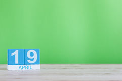 19-ое апреля День 19 месяца, календарь на деревянном столе и предпосылка зеленого цвета Время весны, пустой космос для текста Стоковое фото RF