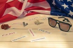 4-ое -го июль, День независимости США, деревянная предпосылка, американский флаг, раковины, выходные, праздники, солнечные очки Стоковая Фотография