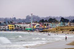 1-ое июля 2018 Santa Cruz/CA/США - толпы имея потеху на пляже и на променаде Santa Cruz на туманный день стоковая фотография