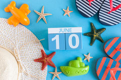 10-ое июня Изображение календаря 10-ое июня на голубой предпосылке с пляжем лета, обмундированием путешественника и аксессуарами  Стоковая Фотография RF