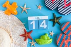 14-ое июня Изображение календаря 14-ое июня на голубой предпосылке с пляжем лета, обмундированием путешественника и аксессуарами  Стоковые Изображения RF