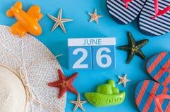 26-ое июня Изображение календаря 26-ое июня на голубой предпосылке с пляжем лета, обмундированием путешественника и аксессуарами  Стоковое Изображение RF