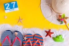27-ое июня Изображение календаря 27-ое июня на желтой песочной предпосылке с пляжем лета, обмундированием путешественника и аксес Стоковые Фотографии RF