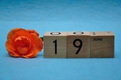 19-ое июня на деревянных блоках с оранжевой розой стоковое изображение rf