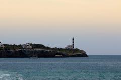 16-ое июня 2017, Порту Colom, Мальорка, Испания - взгляд береговой линии с маяком na górze холма на заходе солнца Стоковые Изображения RF