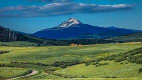 14-ое июля 2016 - бревенчатая хижина с горами и зелеными деревьями - горы Сан-Хуана, Колорадо, США Стоковые Изображения RF