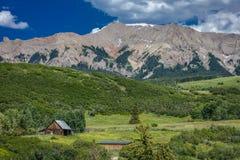 14-ое июля 2016 - бревенчатая хижина с горами и зелеными деревьями - горы Сан-Хуана, Колорадо, США Стоковые Фото