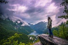 24-ое июля 2015: Путешественник созерцая Geirangerfjord, мир она стоковое фото rf