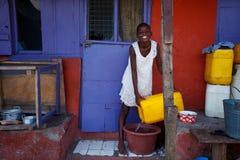 ½ 18-ое марта ¿ ï АККРА, ГАНЫ: Вода неопознанной африканской девушки лить Стоковое Фото
