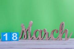 18-ое марта День 18 месяца, ежедневный деревянный календарь на таблице и зеленая предпосылка Время весны, пустой космос для текст Стоковое Фото