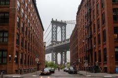 4-ое мая 2019 - США, Нью-Йорк: Мост Манхэттена увиденный от красные кирпичные здания в улице Бруклина в перспективе стоковые изображения rf