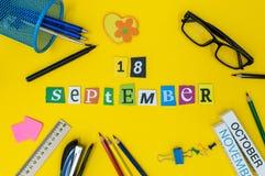 18-ое сентября День 18 месяца, назад к концепции школы Календарь на предпосылке рабочего места учителя или студента с школой Стоковое фото RF