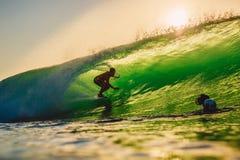 8-ое сентября 2018 bali Индонесия Езда серфера на волне бочонка на заходе солнца Профессиональный серфинг в океане, пляже Bingin стоковая фотография