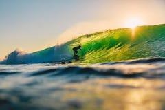 8-ое сентября 2018 bali Индонесия Езда серфера на волне бочонка на заходе солнца Профессиональный серфинг в океане, пляже Bingin стоковое фото