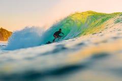 8-ое сентября 2018 bali Индонесия Езда серфера на волне бочонка на заходе солнца Профессиональный серфинг в океане, пляже Bingin стоковые изображения