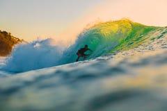 8-ое сентября 2018 bali Индонесия Езда серфера на волне бочонка на заходе солнца Профессиональный серфинг в океане, пляже Bingin стоковая фотография rf