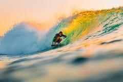 8-ое сентября 2018 bali Индонесия Езда серфера на волне бочонка на теплом заходе солнца Профессиональный серфинг в океане, пляже  стоковая фотография