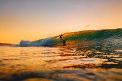8-ое сентября 2018 bali Индонесия Езда серфера на волне бочонка на теплом заходе солнца Профессиональный серфинг в океане, пляже  стоковое изображение