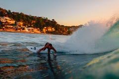 8-ое сентября 2018 bali Индонесия Езда серфера на волне бочонка на теплом заходе солнца Профессиональный серфинг в океане, пляже  стоковая фотография rf