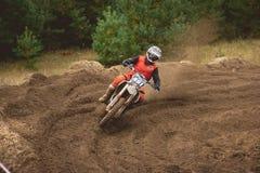 24-ое сентября 2016 - Volgsk, Россия, гонки креста moto MX - всадник мотоцикла в красном костюме приходит к повороту и бросать Стоковая Фотография