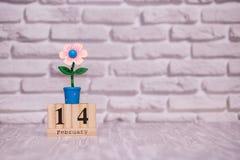 14-ое февраля День 14 месяца на деревянном календаре с цветком игрушки на белой предпосылке кирпича valentines дня счастливые стоковая фотография rf