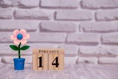 14-ое февраля День 14 месяца на деревянном календаре с цветком игрушки на белой предпосылке кирпича valentines дня счастливые стоковые изображения