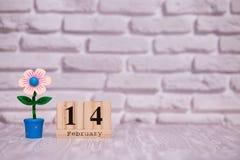 14-ое февраля День 14 месяца на деревянном календаре с цветком игрушки на белой предпосылке кирпича valentines дня счастливые стоковое изображение rf