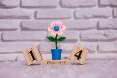 14-ое февраля День 14 месяца на деревянном календаре с цветком игрушки на белой предпосылке кирпича valentines дня счастливые стоковое фото