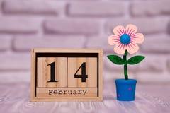 14-ое февраля День 14 месяца на деревянном календаре с цветком игрушки на белой предпосылке кирпича valentines дня счастливые чел стоковое фото