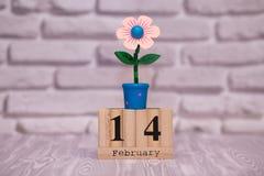 14-ое февраля День 14 месяца на деревянном календаре с цветком игрушки на белой предпосылке кирпича valentines дня счастливые чел стоковая фотография rf