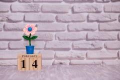 14-ое февраля День 14 месяца на деревянном календаре с цветком игрушки на белой предпосылке кирпича valentines дня счастливые чел стоковое фото rf