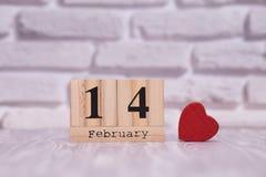 14-ое февраля День 14 месяца на деревянном календаре с цветком игрушки на белой предпосылке кирпича valentines дня счастливые чел стоковое изображение