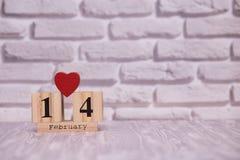 14-ое февраля День 14 месяца на деревянном календаре с цветком игрушки на белой предпосылке кирпича valentines дня счастливые чел стоковые изображения