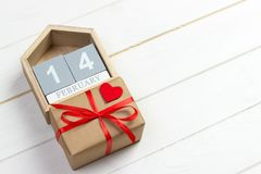14-ое февраля деревянный календарь с красным сердцем и подарочная коробка на верхней карточке дня ` s валентинки скопируйте космо Стоковое фото RF