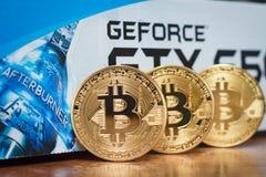18-ое февраля 2018 Москва Россия 3 bitcoins золота на предпосылке упаковки от GeForce GTX Стоковая Фотография