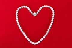 Ожерелье жемчуга на красной предпосылке Стоковые Изображения