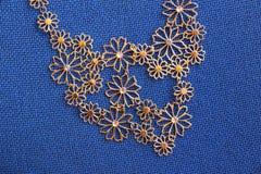 Ожерелье Bijoux на голубой предпосылке ткани Стоковые Изображения