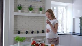 Ожидающая девушка касаясь ее большому положению брюшка около таблицы с фруктами и овощами есть авокадо на кухне сток-видео