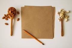 2 ложки с гайками миндалины и анакардии с бумагой и карандашем на белой предпосылке Стоковые Изображения