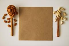 2 ложки с гайками миндалины и анакардии с бумагой на белой предпосылке Стоковые Изображения RF