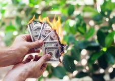 Ожог огня 100 долларов в руке Стоковое Изображение