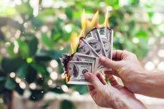 Ожог огня 100 долларов в руке Стоковое Фото