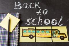 Озаглавьте назад к школе и изображению школьного автобуса нарисованному на кусках бумаги и тетради Стоковые Фото