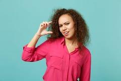 Озадаченная африканская девушка в случайных одеждах показывая жестами демонстрирующ размер с местом для работы изолированным на г стоковая фотография