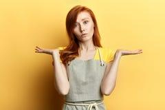 Озадаченная неуверенная девушка с длинными красными волосами в серых рисберме и футболке стоковое фото rf