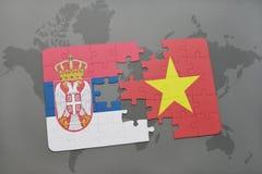 озадачьте с национальным флагом Сербии и Вьетнама на карте мира Стоковое Фото
