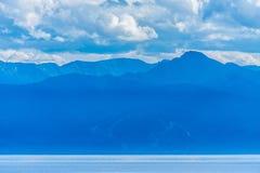Озеро Байкал в сизоватом помохе с силуэтами гор стоковая фотография