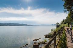Озеро Варезе, ландшафт лета, Италия Озеро, велосипедист и цикл - пешеходный след который бежит вдоль озера стоковые фотографии rf